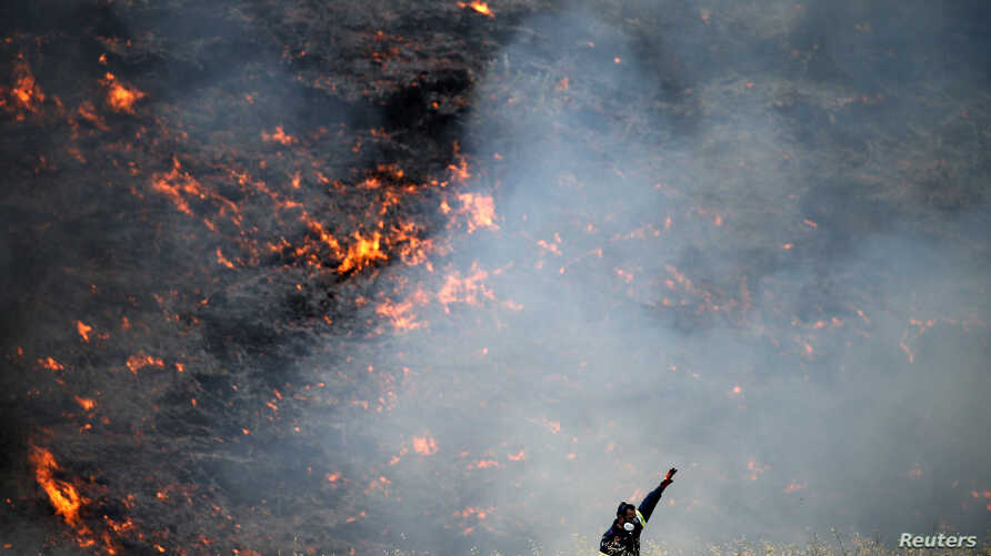 A firefighter reacts during a wildfire near the village of Metochi, north of Athens, Greece, Aug. 14, 2017.