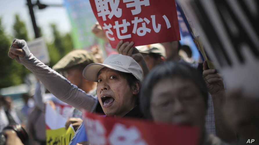 """Hundreds of people stage a rally outside the Japanese Prime Minister's Office in Tokyo, May 14, 2015, protesting a set of controversial bills intended to expand Japan's defense role at home and internationally. A banner, top, reads """"No War."""""""