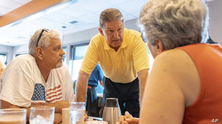 Democratic Sen. Joe Manchin, center, speaks to John Heron and Connie Hill about his recent vote in the Senate to confirm Supreme Court nominee Brett Kavanaugh, Oct. 7, 2018, at an IHOP restaurant in Charleston, W.Va.