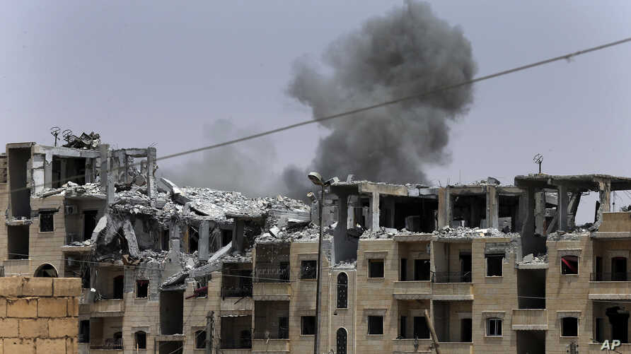 FILE - In this July 17, 2017, photo, smoke rises from a coalition airstrike which attacked an Islamic State position, on the front line on the western side of Raqqa, northeast Syria.
