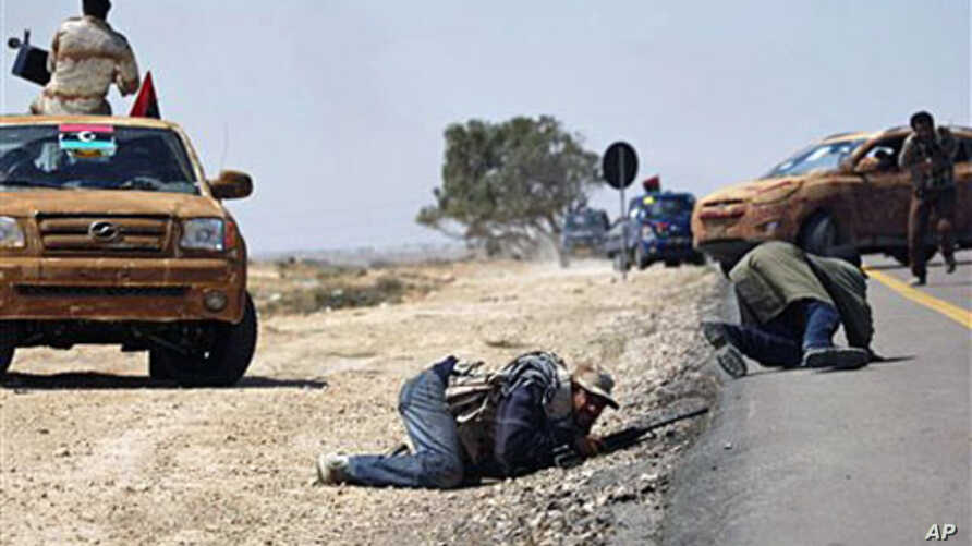 Libyan rebels duck while others retreat during an exchange of fire with pro Gadhafi forces along the frontline at the outskirts of Brega, Apr 4 2011