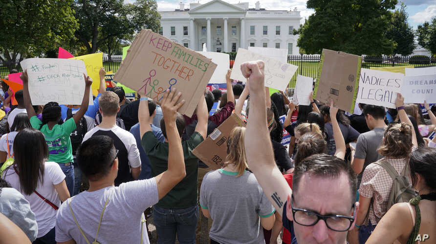 Malcolm McCluskey, right, pumps his fist in the air as he joins in a chant with supporters of Deferred Action for Childhood Arrival program (DACA) during a demonstration on Pennsylvania Avenue in front of the White House in Washington, Sept. 9, 2017.