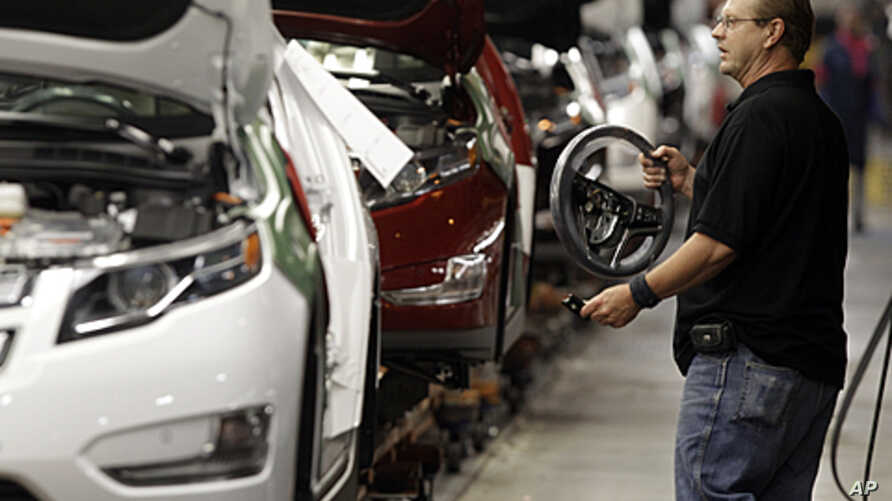 Assembly line worker Gary Phillips carries a steering wheel for a Chevrolet Volt at the General Motors Hamtramck Assembly plant in Hamtramck, Michigan, July 27, 2011.