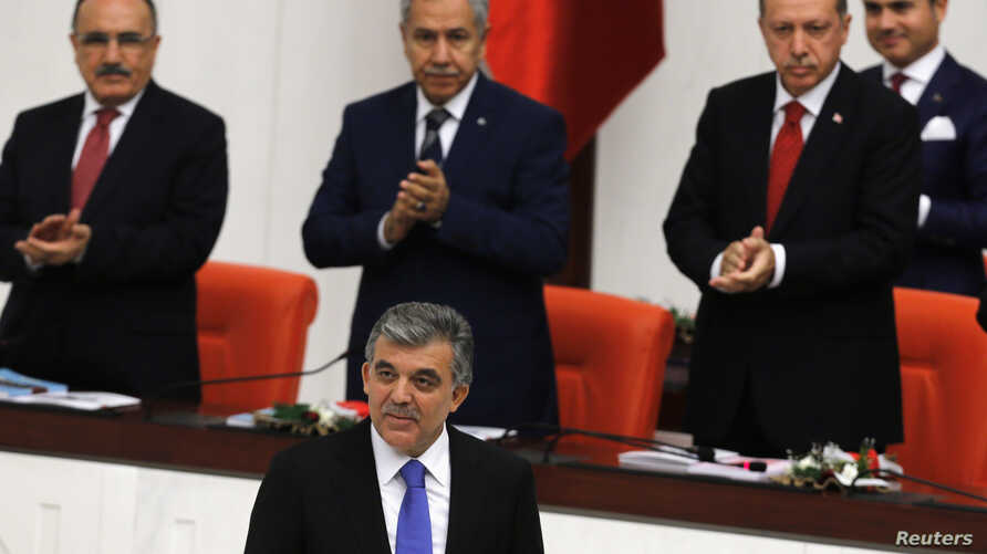 Turkey's President Abdullah Gul (C) is applauded by Prime Minister Tayyip Erdogan (R) and his ministers as he arrives to address the Turkish Parliament during a debate marking the reconvene of the parliament after a summer recess in Ankara, Oct. 1, 2