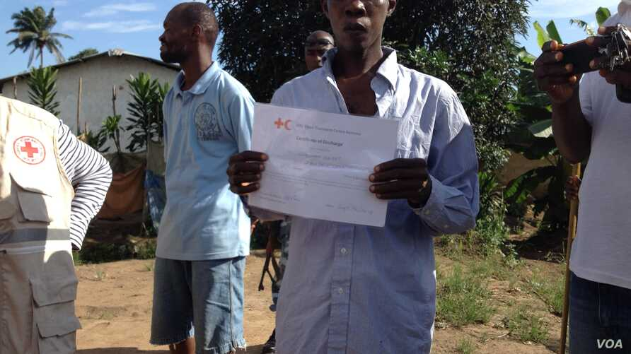 Osman Sesay, an Ebola survivor, holds up his discharge certificate in Banga Ground community, near Freetown, Sierra Leone, Sept., 27, 2014.