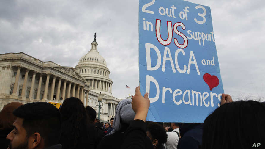 A woman holds up a sign outside the Capitol in support of the Deferred Action for Childhood Arrivals (DACA) program, Dec. 5, 2017, on Capitol Hill in Washington.