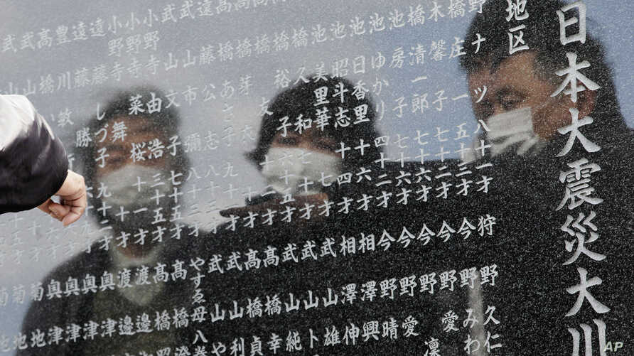 A man points to the name of one of the victims of the earthquake and tsunami inscribed in a cenotaph in Okawa district in Ishinomaki, Miyagi Prefecture, northern Japan, Monday, March 11, 2013.