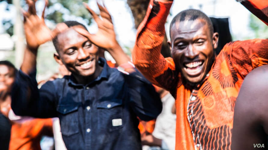 Young people dance on the grounds of the ruling PPRD party campaign office. (C. Oduah/VOA)