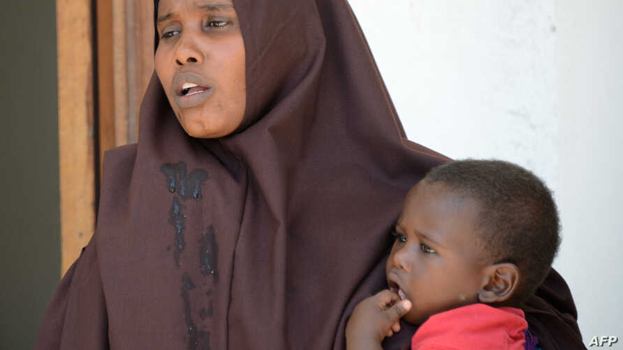 FILE - A Somali woman, who was sentenced to a year in jail after she told a reporter she was raped by security forces, holds her baby at the court house in Mogadishu, March 3, 2013.