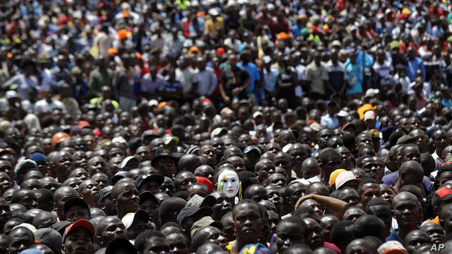 "Supporters of opposition leader Raila Odinga, one wearing a mask, attend a mock ""swearing-in"" ceremony at Uhuru Park in downtown Nairobi, Kenya, Jan. 30, 2018."