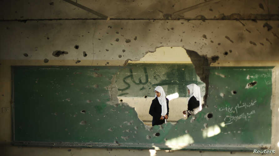 Palestinian students look inside a classroom that witnesses said was shelled by Israel during its offensive, on the first day of the new school year east of Gaza City September 14, 2014.