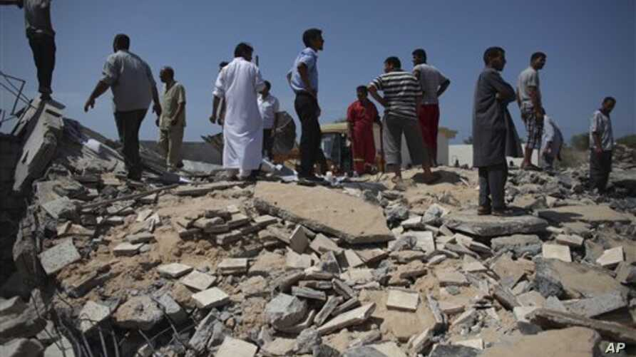 In this photo taken on a government-organized tour, Libyan men stand on top of the remains of a medical clinic that was destroyed during a NATO airstrike early Monday morning, in the town of Zlitan, roughly 160 km (99 miles) east of Tripoli, Libya, M