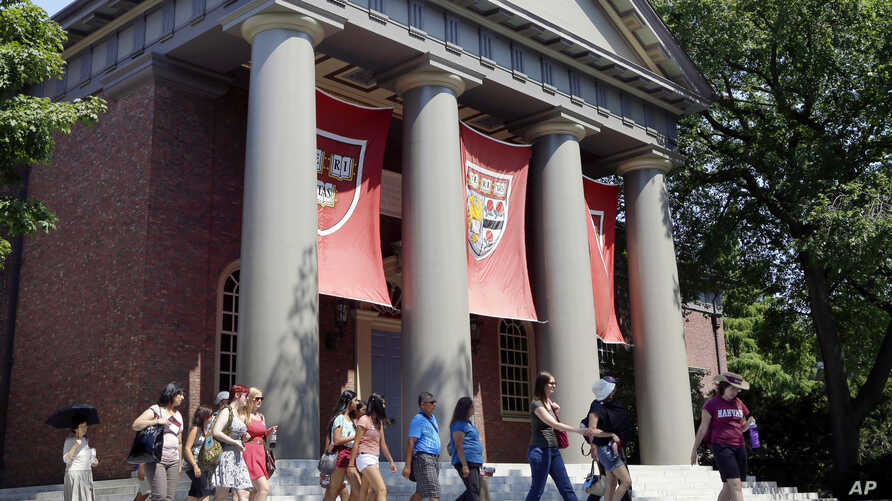 FILE - A tour group walks through the campus of Harvard University in Cambridge, Mass, Aug. 30, 2012. The Justice Department has sided with Asian-American students suing Harvard University over the Ivy League school's consideration of race in its adm