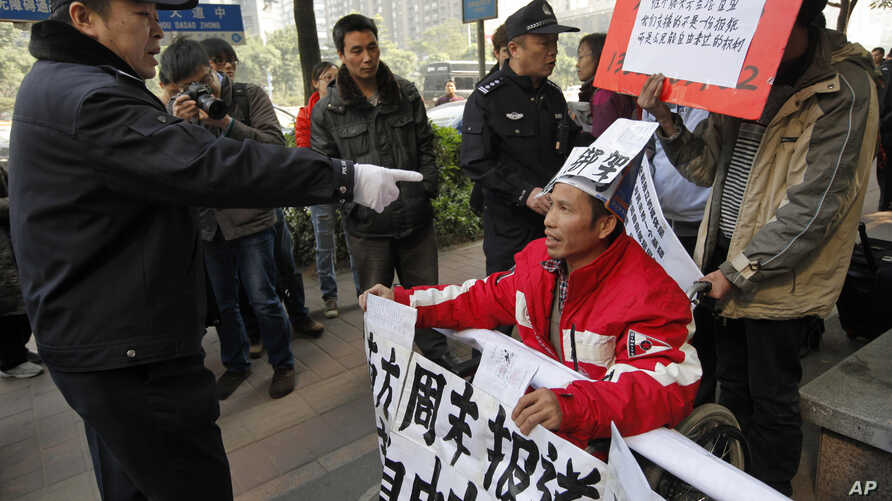 A policeman points to a supporter of Southern Weekly newspaper in a wheelchair before taken him away during a protest near the headquarters of the newspaper in Guangzhou, Guangdong province, China, Jan. 10, 2013.