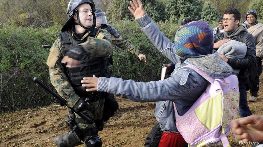 A Macedonian police officer hits a stranded migrant attempting to cross the Greek-Macedonian border, near Gevgelija, Macedonia December 2, 2015.