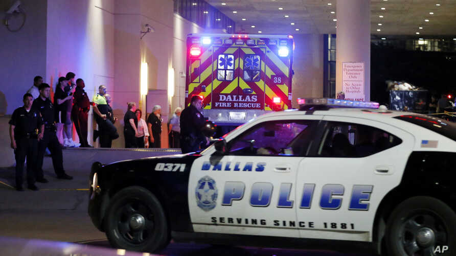 A Dallas police vehicle follows behind an ambulance carrying a patient to the emergency department at Baylor University Medical Center, as police and others stand near the emergency entrance early Friday, July 8, 2016.