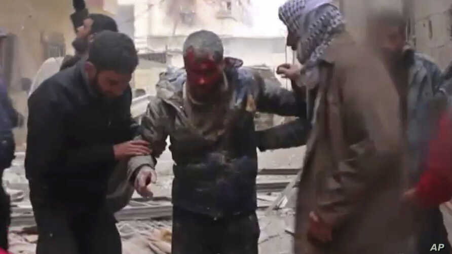 In this frame grab from video released Jan. 1, 2018 by the Syrian Civil Defense group, known as the White Helmets, Syrians help an injured man on a stretcher after an airstrike hit the Damascus suburb of Masraba, Syria.