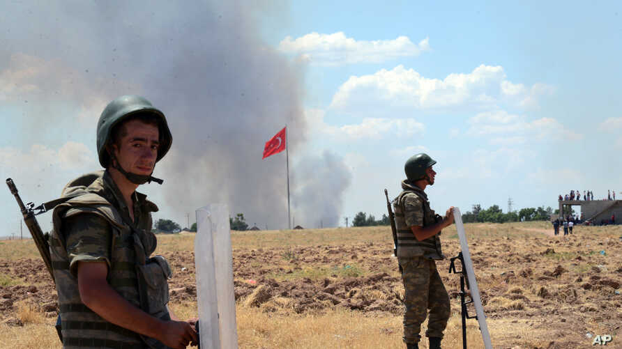 Turkish soldiers stand guard on the Turkish side of the border in Suruc, Turkey, June 26, 2015, as smoke rises in the background.