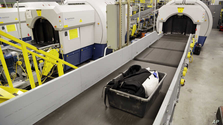 FILE - Luggage emerges on a conveyer belt after passing through a CTX scanner at John F. Kennedy International Airport in New York, Oct. 30, 2014.