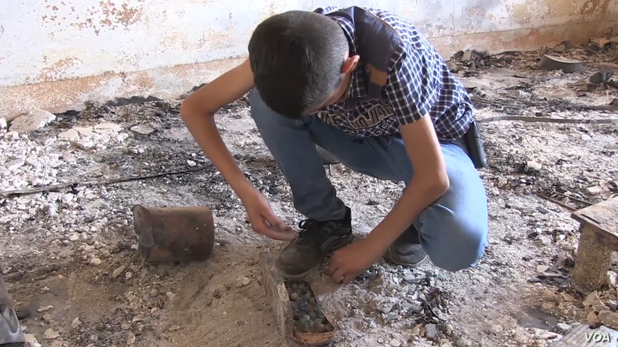 Noeh Binoo, 13, squats to collect remains of his marbles in what used to be his bedroom before Islamic State militants torched it three years ago. August 2017 (Open Doors USA photo)