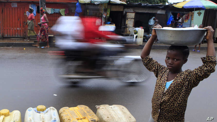 FILE - A young vendor walks past jerrycans of water for sale in central Monrovia, Liberia. Improvements in road maintenance are a major element of the MCC.