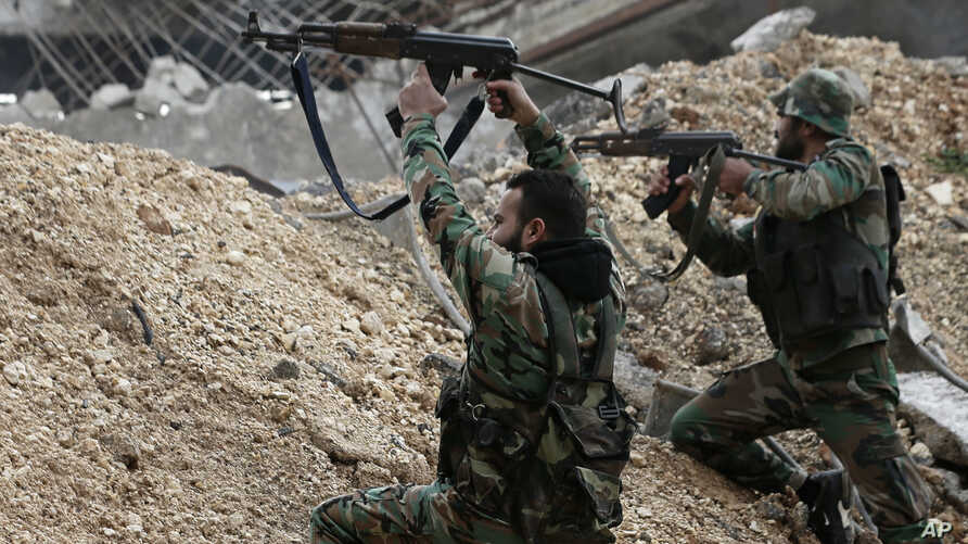 Syrian army soldiers fire their weapons during a battle with rebel fighters at the Ramouseh front line, east of Aleppo, Syria, Dec. 5, 2016.