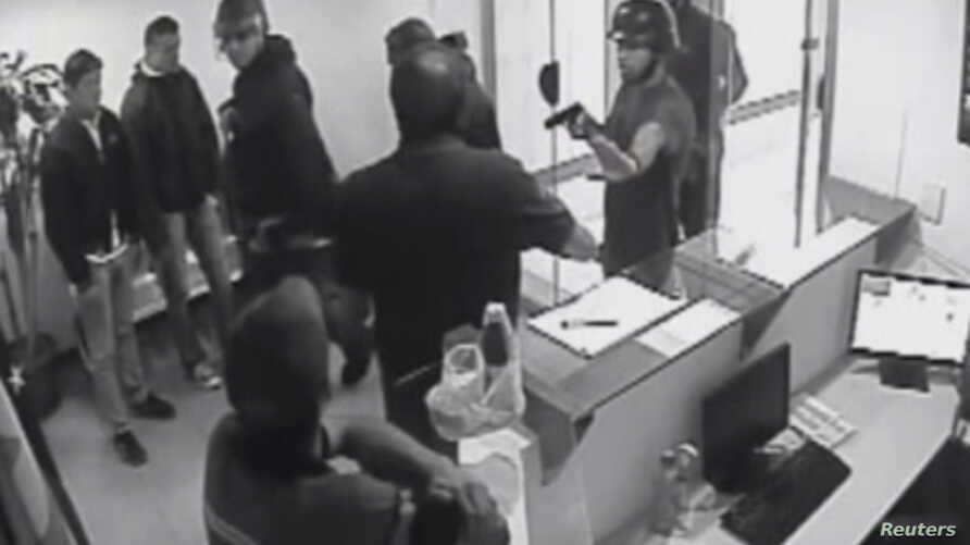 This video grab from a security camera shows the moment where armed police break-in to Voluntad Popular (Popular Will) headquarters in Caracas, Feb. 17, 2014.  Videos sent to media by Popular Will, which could not be independently identified, showed