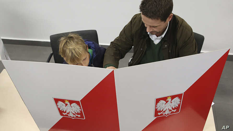 The candidate for Warsaw mayor for the pro-European Union Civic Platform party, Rafal Trzaskowski, with his son Stasio, check voting lists in local elections that were the test of support for the ruling right-wing Law and Justice party, whose policie