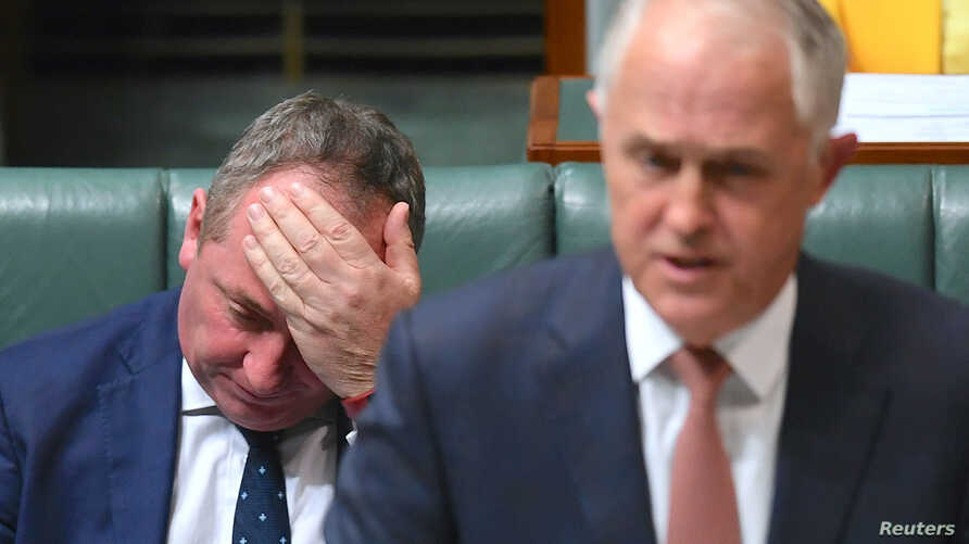Australian Deputy Prime Minister Barnaby Joyce reacts as he sits behind Australian Prime Minister Malcolm Turnbull in the House of Representatives at Parliament House in Canberra, Australia, Oct. 24, 2017.