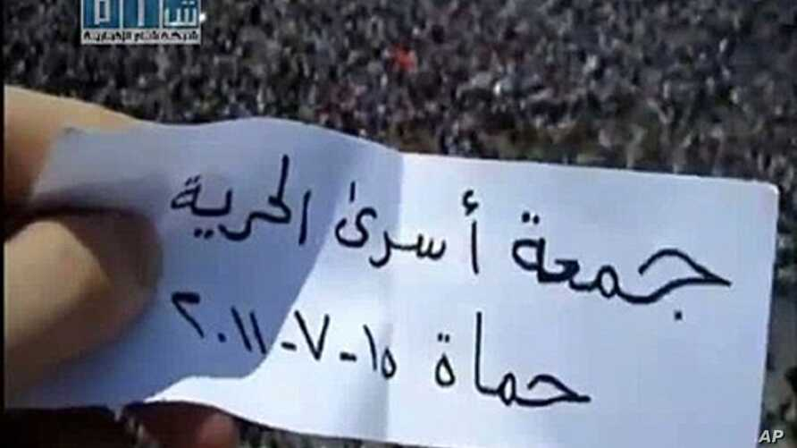 An image taken from footage uploaded on YouTube by the Shams News Network (SNN) shows a Syrian anti-government protester holding a piece of paper which says in Arabic 'Friday of Prisoner Freedom, Hama, July 15, 2011' on a rooftop above thousands of p