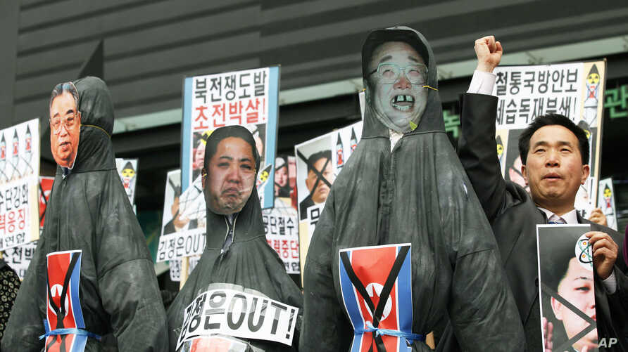 South Korean protesters display effigies of North Korean leader Kim Jong Un, center, and late leaders Kim Jong Il, right, and Kim Il Sung at an anti-North Korea protest on the birthday of Kim Il Sung in Seoul, South Korea, April 15, 2013.