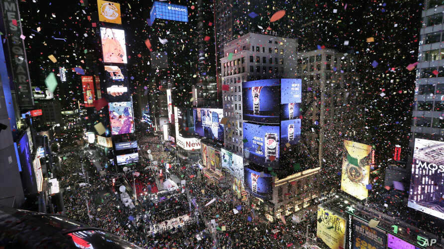 FILE - Confetti drops over the crowd at midnight during the New Year's celebration in Times Square as seen from the Marriott Marquis in New York, Jan. 1, 2018.