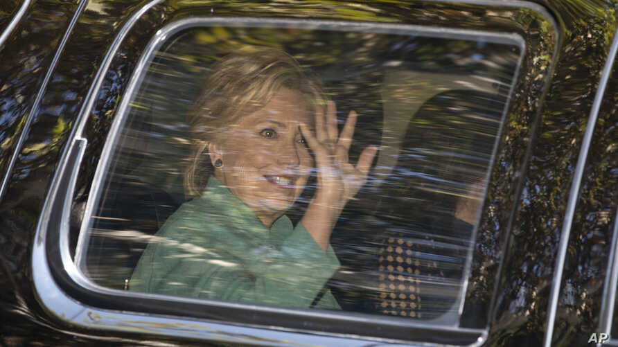 Democratic presidential candidate Hillary Clinton waves from her motorcade vehicle as she arrives for a fundraiser at the home of Justin Timberlake and Jessica Biel in Los Angeles, Aug. 23, 2016.