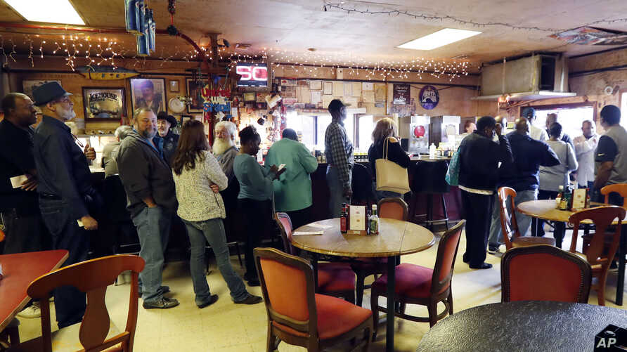 Lottery players line up to purchase Mega Millions lottery tickets, at The World Bar and Grill, in Delta, La., a few miles from the Mississippi-Louisiana state line, Oct. 23, 2018.