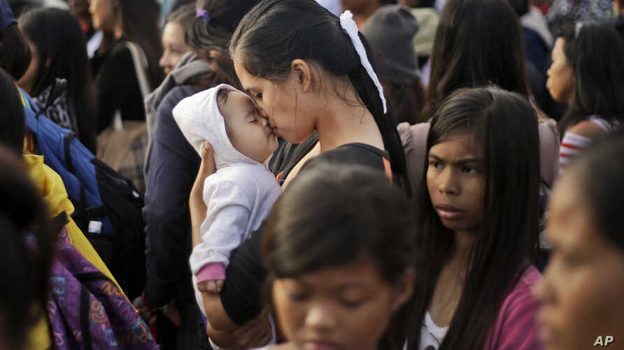 A Typhoon Haiyan survivor kisses her baby as she waits to board her evacuation flight at the airport in Tacloban, Philippines, Nov. 22, 2013.