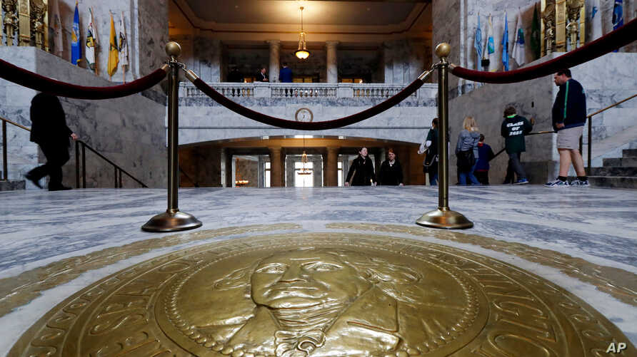 FILE - In this March 8, 2018, photo, visitors walk past the Washington state seal in the Capitol Rotunda in Olympia, Washington. Washington's legislative session is over but the conversation about sexual harassment at the state Capitol continues.