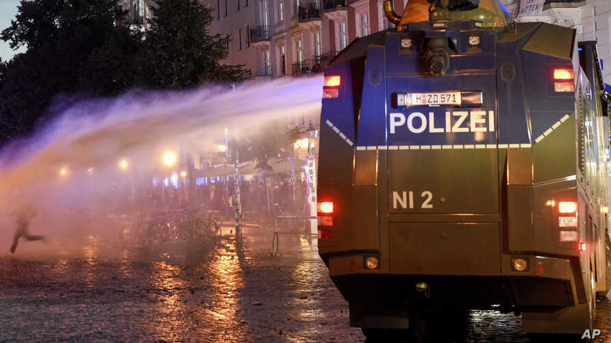 Protesters confront a police water cannon during anti G-20 demonstrations in Hamburg, Germany, July 8, 2017.