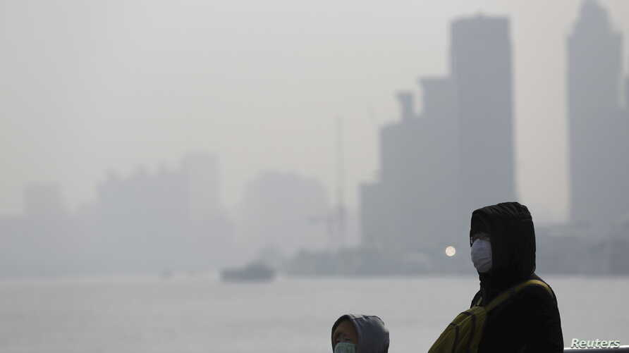 People wear protective masks near the Bund during a polluted day in Shanghai, China, Jan. 19, 2016. Environmentalists have warned that dirty water is a greater problem than dirty air, and China's top court reaffirmed a record fine on six firms for po