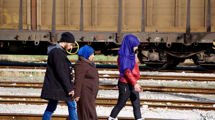 A Syrian family walk back down the tracks away from Macedonia after being told the border won't open today. (Jamie Dettmer for VOA)