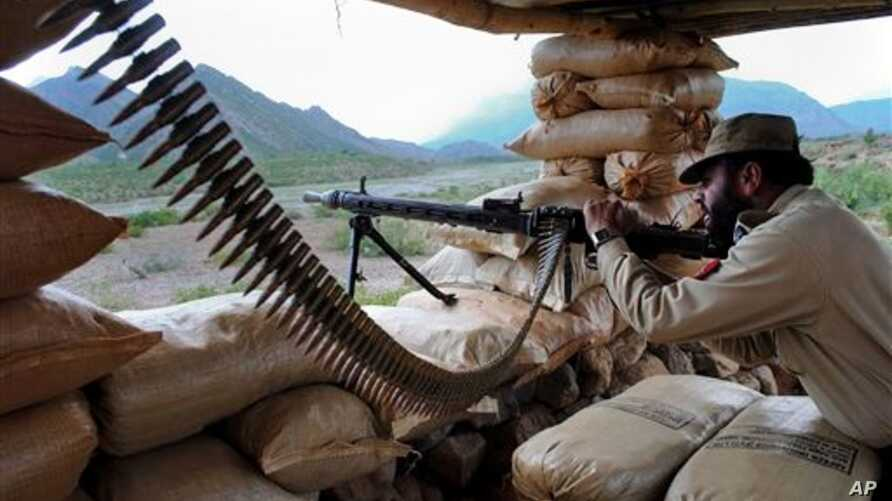 A Pakistani paramilitary soldier prepares to fire during a military operation against militants in Pakistan's Khurram tribal region, Saturday, July 9, 2011