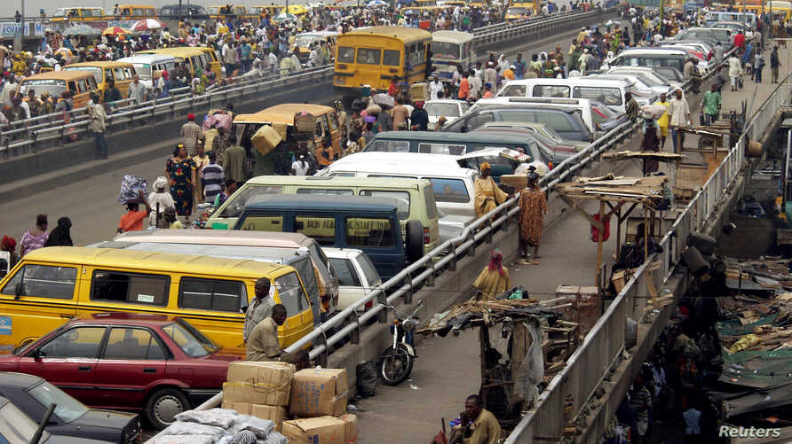 Commuters and traders park their vehicles on the Ido bridge in Lagos, Nigeria, Feb. 7, 2003.