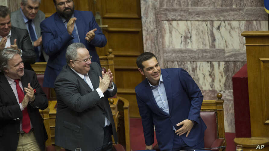 Greek Prime Minister Alexis Tsipras, right, is applauded by lawmakers after the end of his speech during a parliamentary session, in Athens, June 16, 2018.