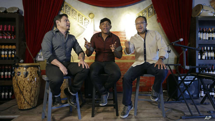 Members of the Colombian salsa band Sonora Carruseles, Leonardo Sierra, left, Daniel Marmolejo, center, and Jans Certuche, right, sing one of their hits during an interview in Doral, Fla, AUg. 17, 2015.