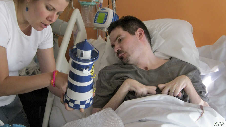 A handout photo taken on September 28, 2014 by the parents of Vincent Lambert (R) and released by their lawyer Jean Paillot shows Vincent Lambert, a quadriplegic man on artificial life support, with his sister Marie Lambert (L) at a hospital in Reims
