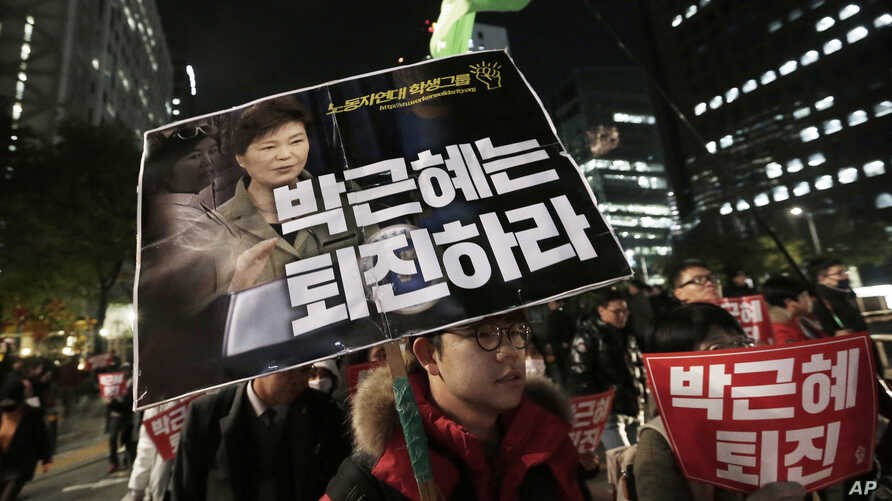 A South Korean protester carries a placard showing images of South Korean President Park Geun-hye and Choi Soon-sil, top left, during a rally calling for Park to step down, Nov. 2, 2016, in Seoul, South Korea.