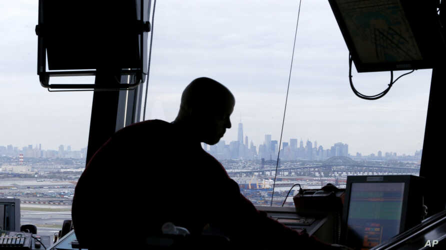FILE - In this May 21, 2015 file photo, an air traffic controller works in the tower at Newark Liberty International Airport in Newark, N.J.