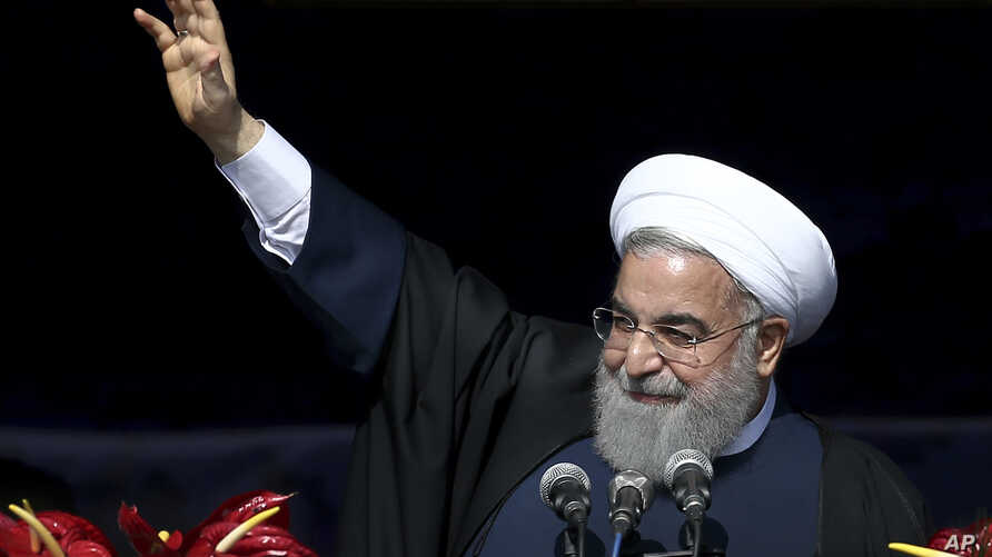Iranian President Hassan Rouhani waves to the crowd during a rally marking the 39th anniversary of the 1979 Islamic Revolution, in Tehran, Iran, Sunday, Feb. 11, 2018. Hundreds of thousands of Iranians rallied on the streets Sunday to mark the annive