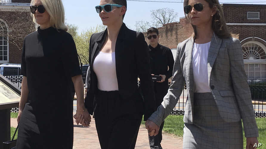 Actress Rose McGowan, flanked by lawyers Jennifer Robinson, left, and Jessica Carmichael, right, outside the Loudoun County courthouse in Leesburg, Virginia, May 3, 2018.