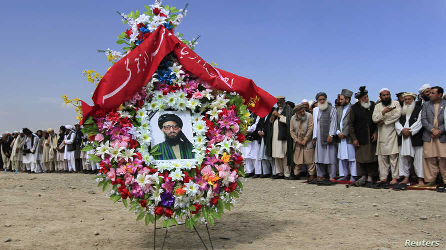 A portrait of former Taliban minister Maulvi Arsala Rahmani, a senior member of the High Peace Council, is seen as officials and mourners perform funeral prayers over the coffin in Kabul.