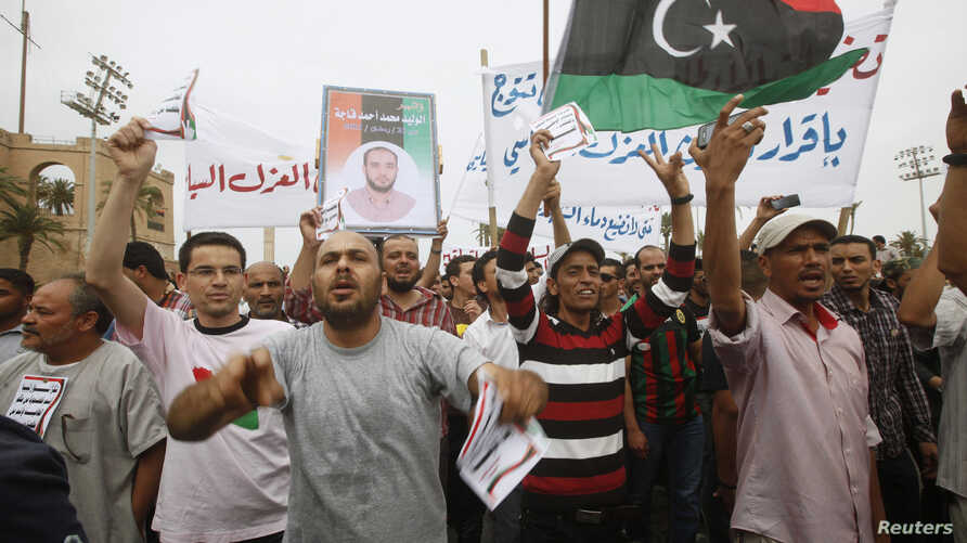 Protesters wave a Libyan flag as they demonstrate in Martyrs' Square demanding Gadhafi-era officials to be banned from taking up political posts, in Tripoli, Libya, May 5, 2013.